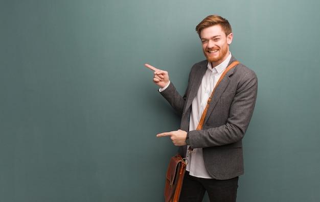Jonge roodharige bedrijfsmens die aan de kant met vinger richt