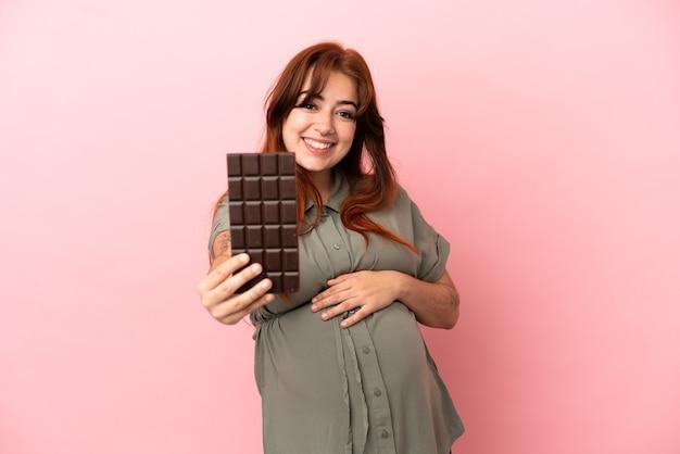 Jonge roodharige blanke vrouw geïsoleerd op roze achtergrond zwanger en met chocolade