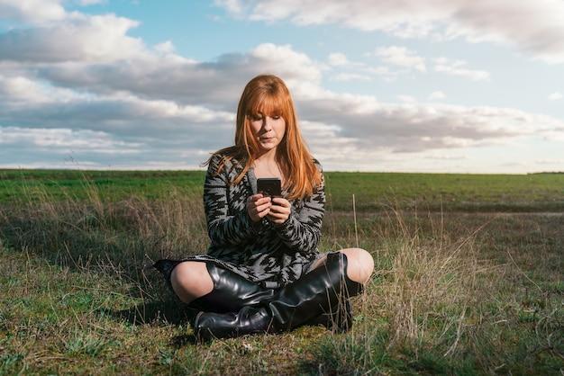Jonge roodharige blanke vrouw zittend op het gras in een veld met haar telefoon gekleed in cowboylaarzen onder een met wolken bedekte hemel