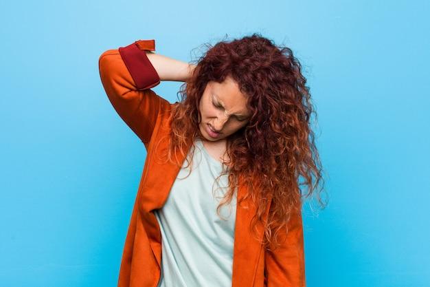 Jonge roodharige elegante vrouw die aan nekpijn lijdt vanwege een zittende levensstijl.
