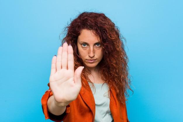 Jonge roodharige elegante vrouw die zich met uitgestrekte hand bevindt die stopbord toont, dat u verhindert. Premium Foto