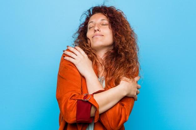 Jonge roodharige elegante vrouw knuffels, glimlachend zorgeloos en gelukkig.