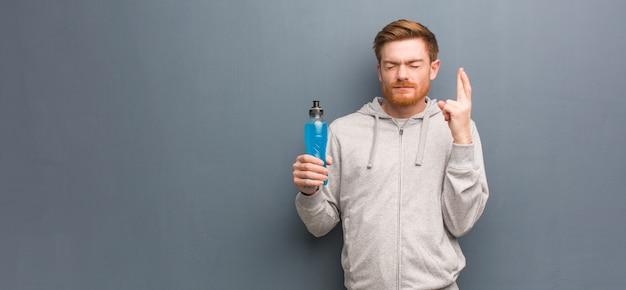Jonge roodharige fitness man die vingers kruist om geluk te hebben. hij houdt een energiedrankje vast.