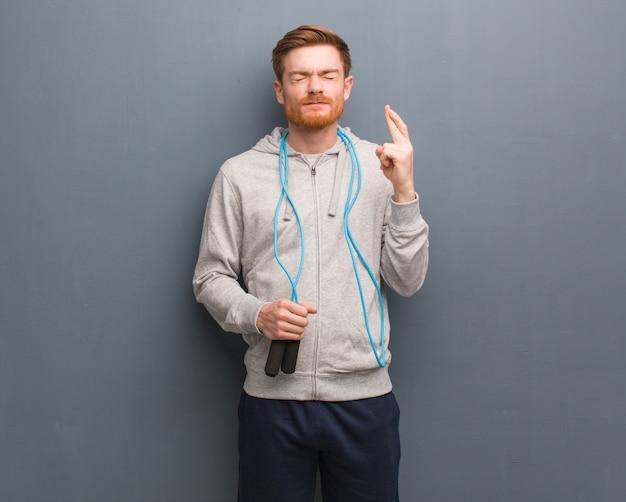 Jonge roodharige fitness man kruising vingers voor het hebben van geluk