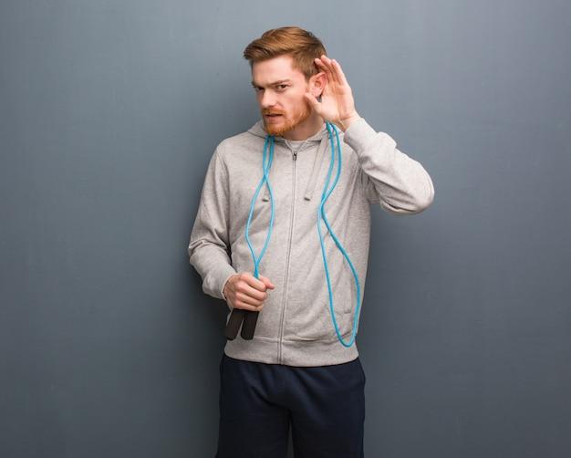 Jonge roodharige fitness man probeert te luisteren naar een roddel. hij houdt een springtouw vast.