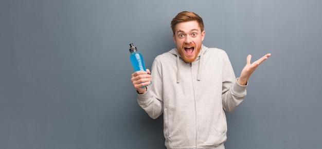 Jonge roodharige fitness man viert een overwinning of een succes. hij houdt een energiedrank vast.