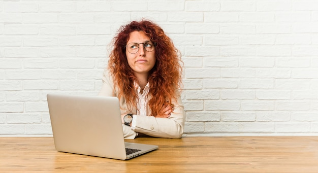 Jonge roodharige krullende vrouw die met haar laptop het ongelukkige kijken in camera met sarcastische uitdrukking werkt.
