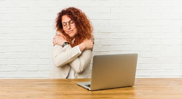 Jonge roodharige krullende vrouw die met haar laptop omhelzingen werkt, onbezorgd en gelukkig glimlacht.
