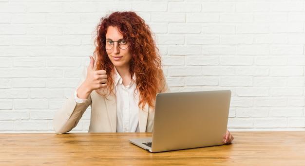 Jonge roodharige krullende vrouw die met haar laptop werkt die en duim glimlacht opheft