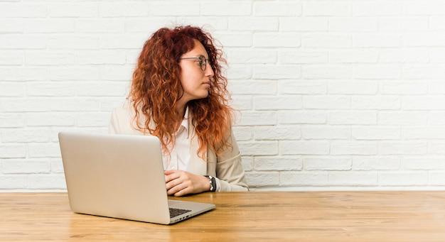 Jonge roodharige krullende vrouw die met haar laptop werkt die naar links staart