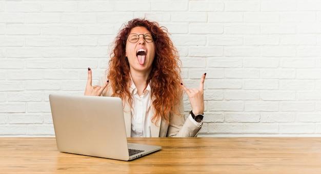 Jonge roodharige krullende vrouw die met haar laptop werkt die rotsgebaar met vingers toont