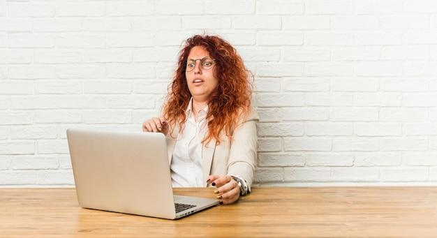 Jonge roodharige krullende vrouw die met haar laptop werkt die wordt geschokt als gevolg van een dreigend gevaar