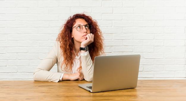 Jonge roodharige krullende vrouw die met haar laptop werkt die zijdelings met twijfelachtige en sceptische uitdrukking kijkt.