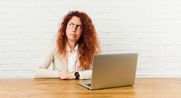 Jonge roodharige krullende vrouw die met haar verwarde laptop werkt, voelt twijfelachtig en onzeker.