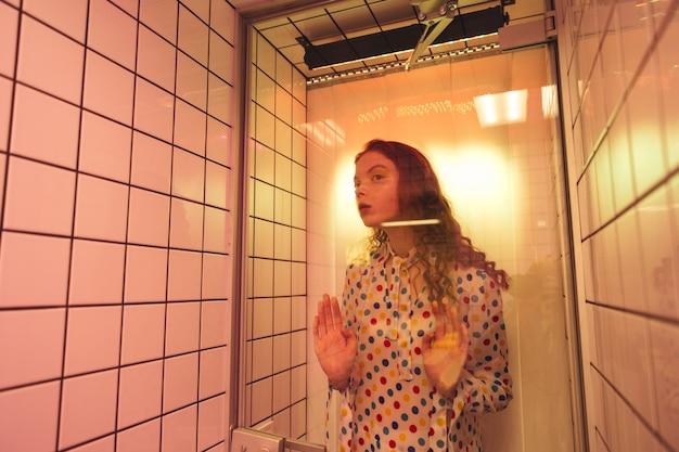 Jonge roodharige krullende vrouw die zich in koffie bij latrine bevindt