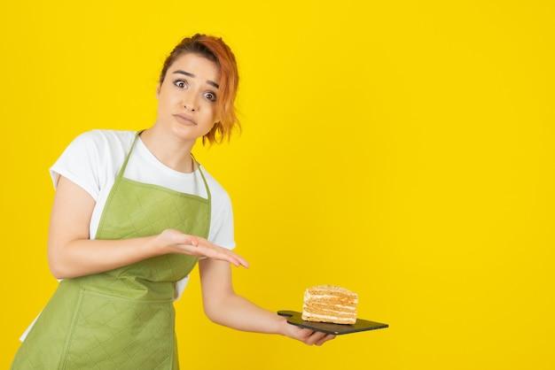 Jonge roodharige lijkt bang en houdt een vers stuk cake vast
