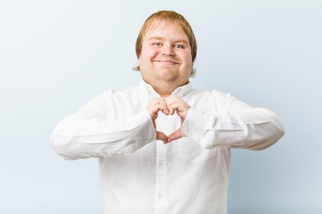 Jonge roodharige man die lacht en een hartvorm met handen toont