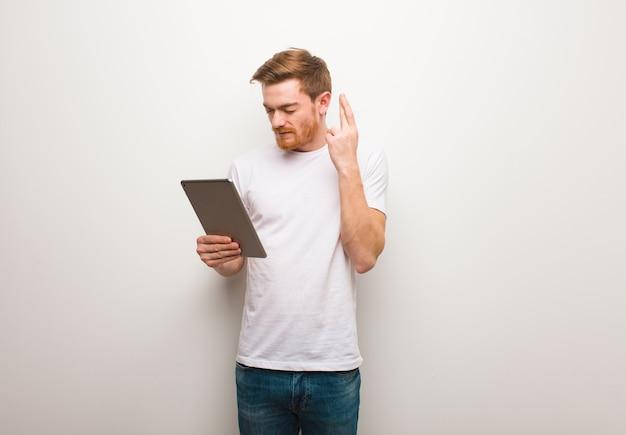 Jonge roodharige man die vingers kruist omdat hij geluk heeft. een tablet vasthouden.