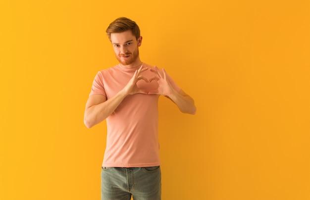 Jonge roodharige man doet een hartvorm met handen