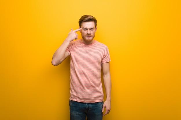 Jonge roodharige man doet een teleurstelling gebaar met vinger