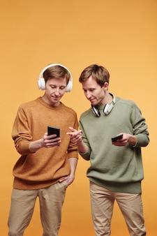 Jonge roodharige man in draadloze koptelefoon met telefoonscherm en muzieknummer delen met tweelingbroer