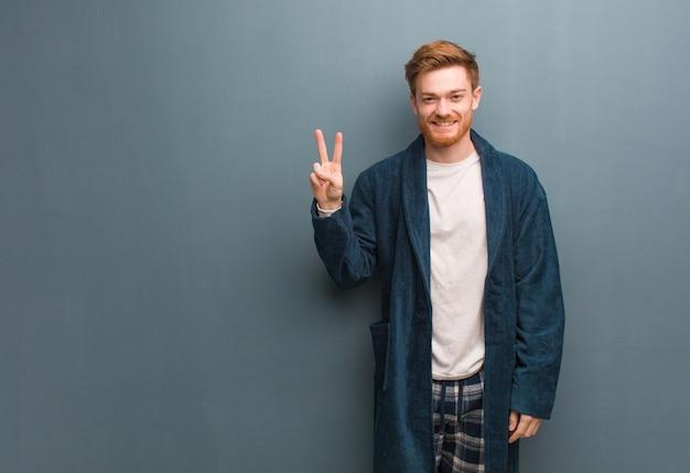 Jonge roodharige man in pyjama met nummer twee