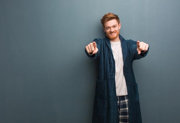 Jonge roodharige man in pyjama vrolijk en glimlachend wijzend naar voren