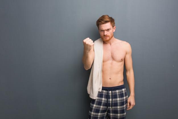 Jonge roodharige man met een handdoek met vuist naar voren, boze uitdrukking. hij houdt een witte handdoek vast.