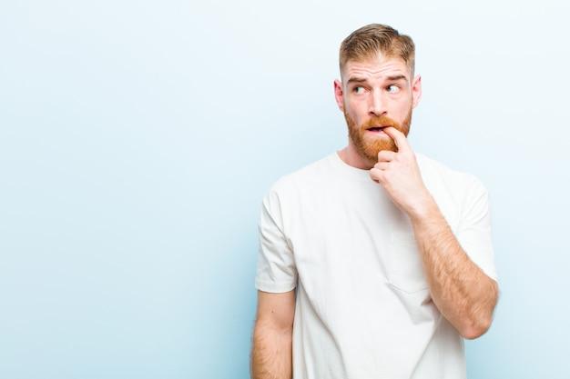 Jonge roodharige man met een verbaasde, nerveuze, bezorgde of angstige blik, op zoek naar de kant naar kopie ruimte op zacht blauw