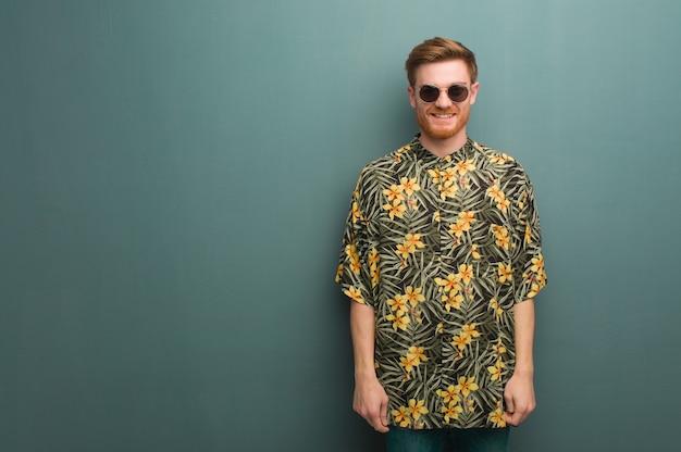 Jonge roodharige man met exotische zomerkleding vrolijk met een grote glimlach