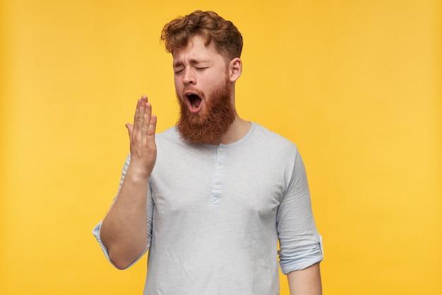 Jonge roodharige man met grote baard met een bange gezichtsuitdrukking, houdt zijn ogen wijd open