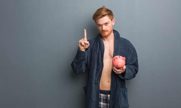 Jonge roodharige man met pyjama met nummer één. hij houdt een spaarvarken vast.