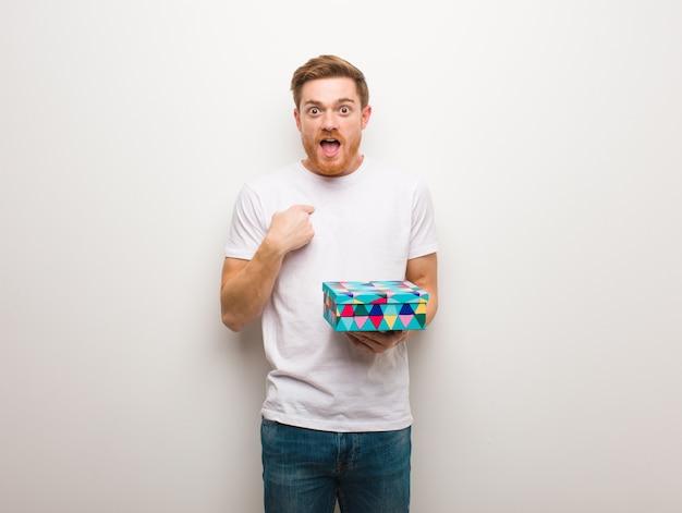 Jonge roodharige man verrast, voelt zich succesvol en welvarend. een geschenkdoos vasthouden.