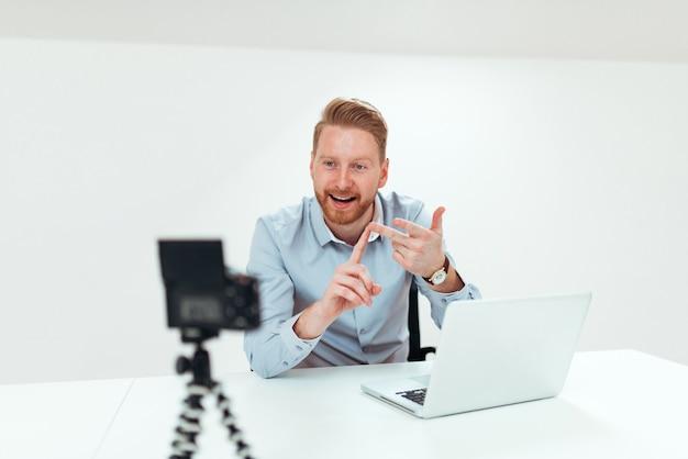 Jonge roodharige man video opnemen voor zijn vlog in heldere ruimte.