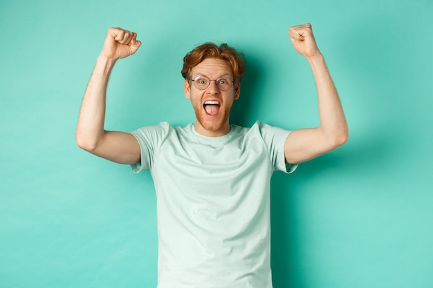 Jonge roodharige man voelt zich als kampioen, steekt zijn handen op in vuistpompgebaar en schreeuwt ja van vreugde, wint prijs, triomfeert van succes, staande over muntachtergrond.