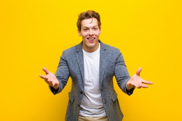 Jonge roodharige man voelt zich gelukkig, verbaasd, gelukkig en verrast, zoals serieus omg zeggen? ongelofelijk oranje