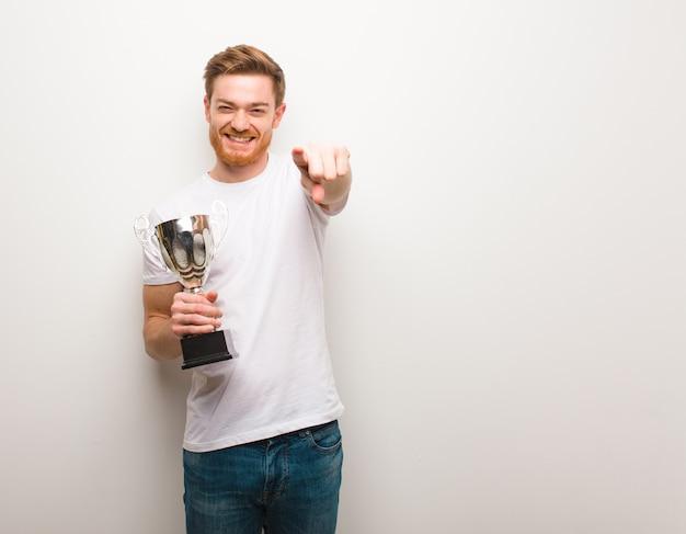 Jonge roodharige man vrolijk en glimlachend wijst naar voorzijde. een trofee houden.