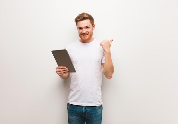 Jonge roodharige man wijst naar de kant met vinger. een tablet vasthouden.