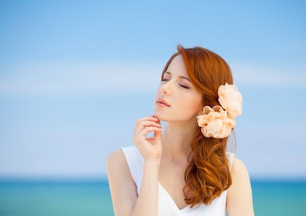 Jonge roodharige meisje in witte jurk en bloem in haar rust op zomer zee strand