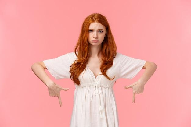 Jonge roodharige meisje met droevige uitdrukking wijst naar iets
