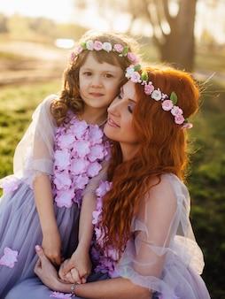 Jonge roodharige moeder met haar dochter die op aard in de zon rust