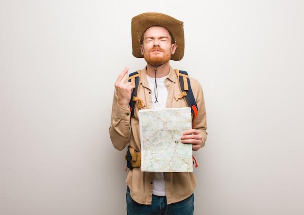 Jonge roodharige ontdekkingsreiziger die vingers kruist omdat hij geluk heeft. een kaart vasthouden.