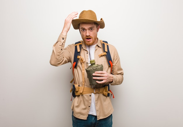 Jonge roodharige ontdekkingsreiziger man bezorgd en overweldigd. hij houdt een veldfles vast.