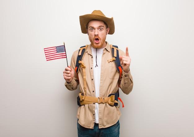 Jonge roodharige ontdekkingsreiziger man met een geweldig idee, concept van creativiteit. met een vlag van verenigde staten.