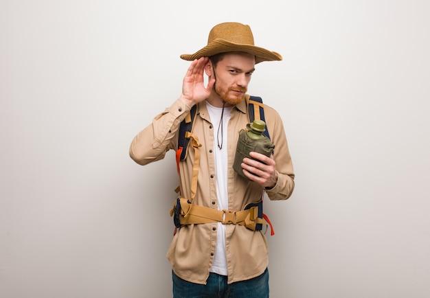 Jonge roodharige ontdekkingsreiziger man probeert te luisteren naar een roddel. hij houdt een veldfles vast.