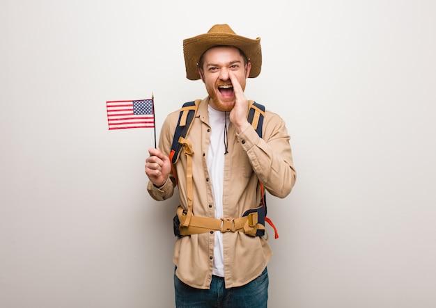 Jonge roodharige ontdekkingsreiziger man schreeuwen iets blij naar de voorkant. een vlag van de verenigde staten vasthouden. Premium Foto