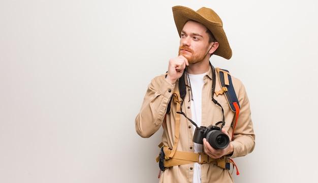Jonge roodharige ontdekkingsreiziger man twijfelen en verward. een camera vasthouden.