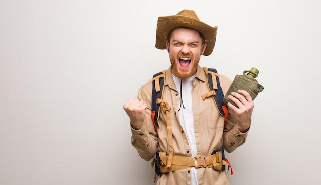 Jonge roodharige ontdekkingsreiziger man verrast en geschokt. hij houdt een veldfles vast.