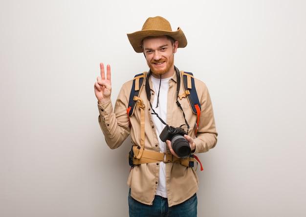 Jonge roodharige ontdekkingsreiziger man weergegeven: nummer twee. een camera vasthouden.