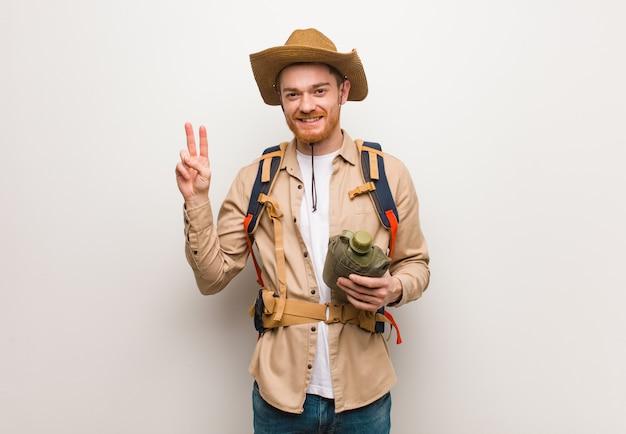 Jonge roodharige ontdekkingsreiziger man weergegeven: nummer twee. hij houdt een veldfles vast.